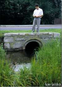 A person stands on the structure above a large storm drain surrounded by grass